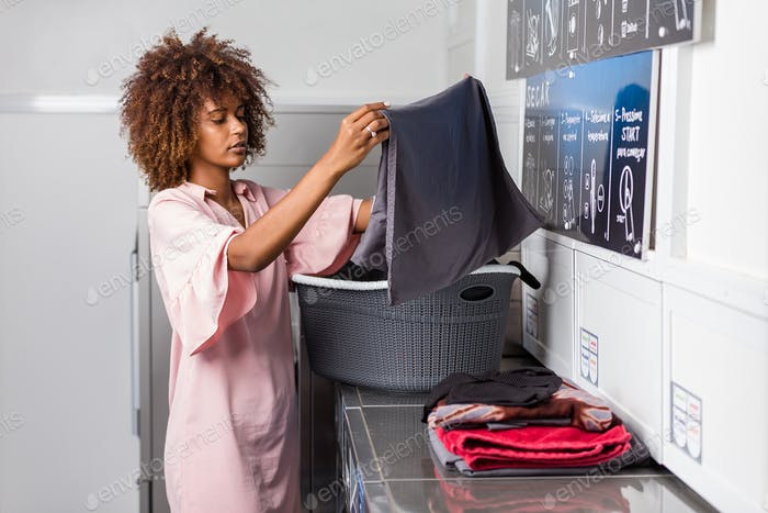 Young black African American woman washing her clothes in a auto