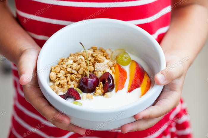 Healthy Breakfast. Fresh Granola, Muesli with Yogurt, Fruits and Berries in Little Girl's Hands.