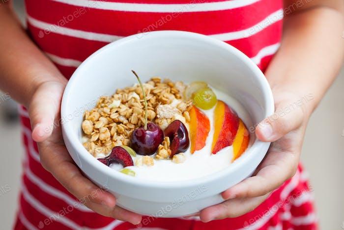 Healthy Breakfast. Fresh Granola, Muesli with Yogurt, Fruits and Berries in Little Girl's Hands.