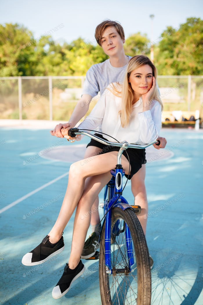 Beautiful boy and girl on bicycle dreamily looking in camera spending time on basketball court