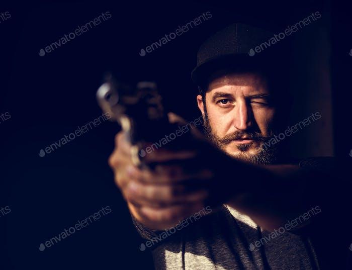 Man holding a gun wth black background