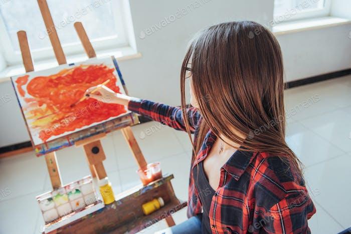 Довольно довольно девушка художник рисует на холсте живопись на мольберт
