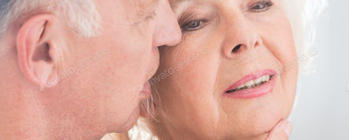 Elderly man whispering to wife