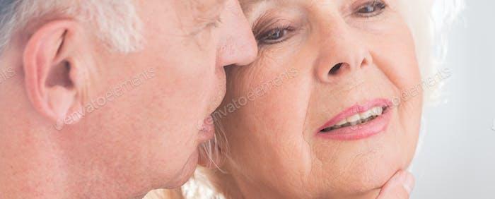 Älterer Mann flüstert Frau