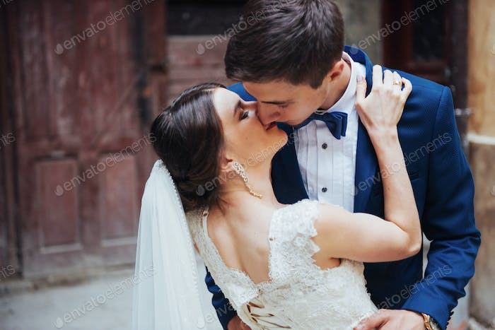 Wedding portrait of a happy couple. Stand and kissing
