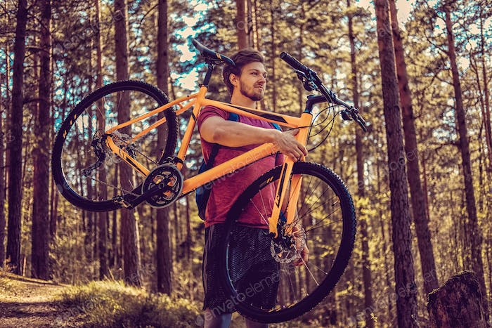 Positive sporty male holding yellow mountain bicycle.