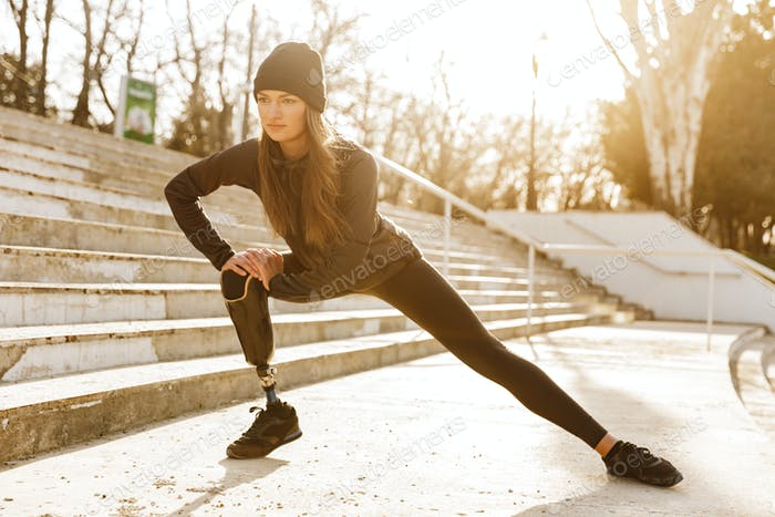 Image of disabled athletic girl in sportswear, doing sit ups and