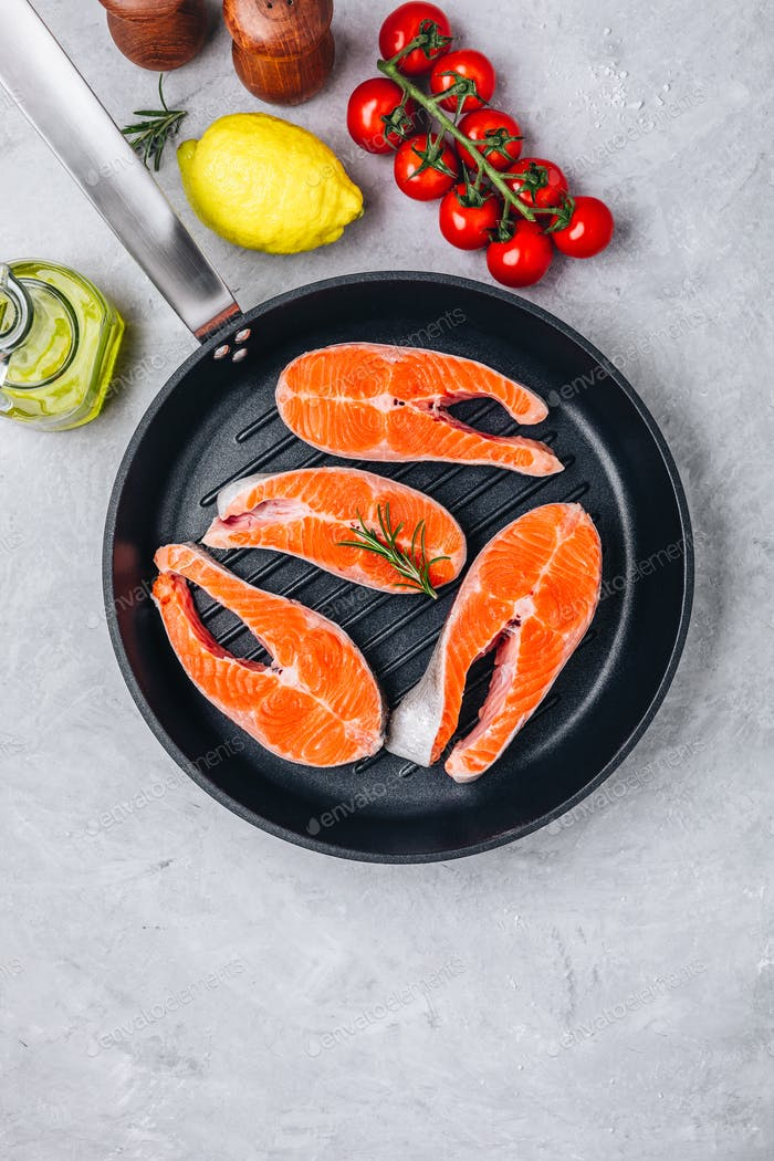 Fresh raw salmon steaks with lemon and rosemary and tomatoes in grill pan on gray background.