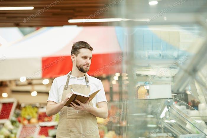 Supermarket Worker doing Inventory