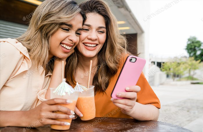 Two friends using phone at coffee shop outdoors.
