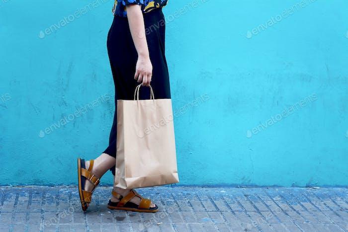 Junge Frau zu Fuß mit Einkaufstaschen