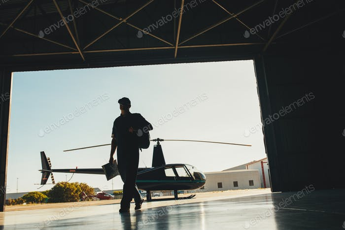 Helicopter pilot arriving at airplane hangar