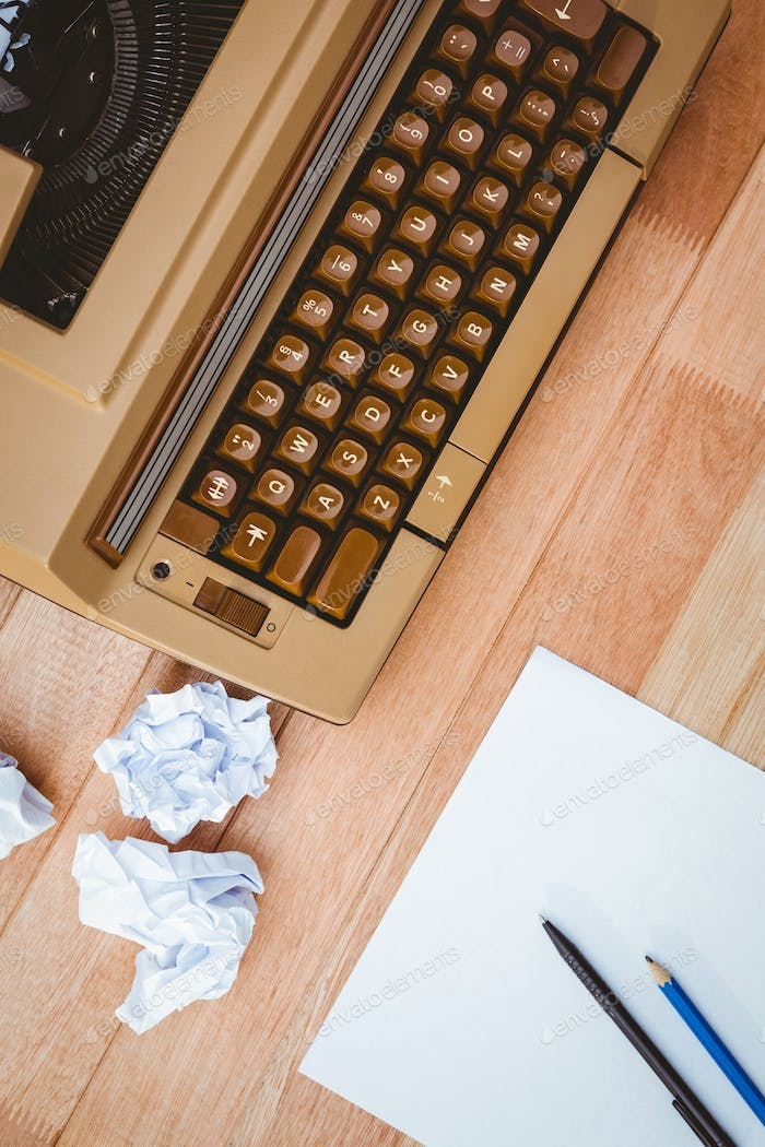 View of an old typewriter and paper on wood desk