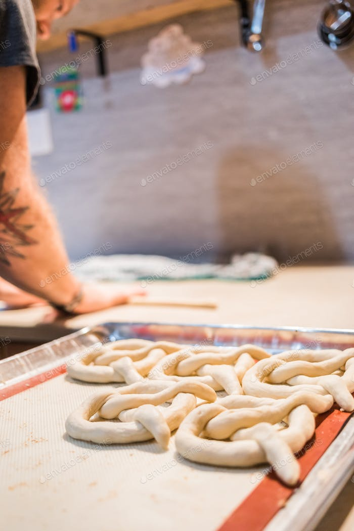 Crop unrecognizable person preparing pretzels.