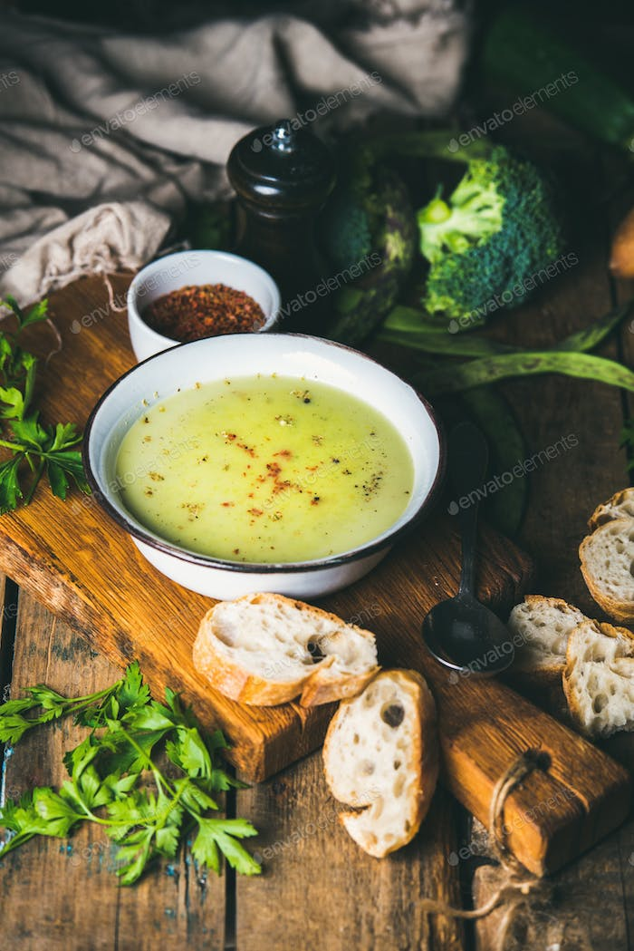 Homemade pea, broccoli, zucchini cream soup with baguette slices