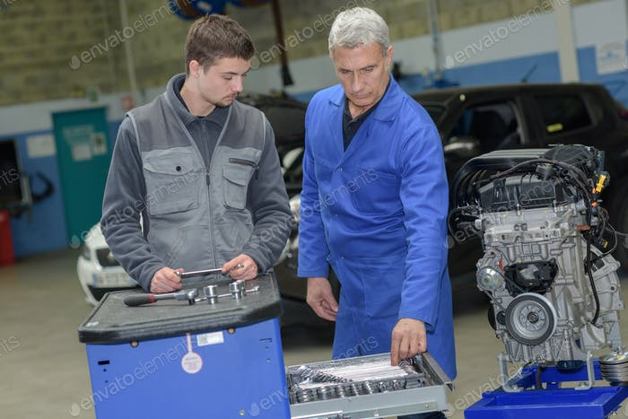 auto mechanic shows trainee maintenance of car engine