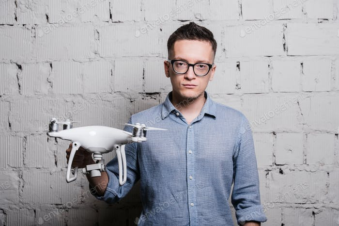 Young stylish Man in glasses holding the quadcopter drone DJI Phantom 4 on a grey brick wall