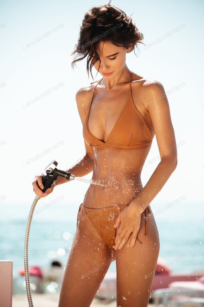 Portrait of pretty lady in beige swimsuit rinsing beach sand off her body on beach