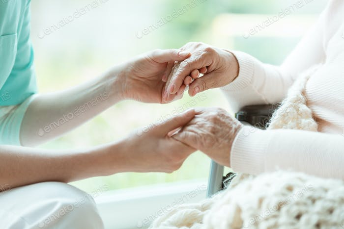 Nurse holding patient's hands