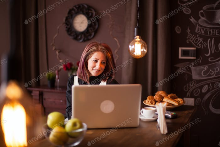 Adult entrepreneur woman smiling at her laptop next to a bowl of green appels