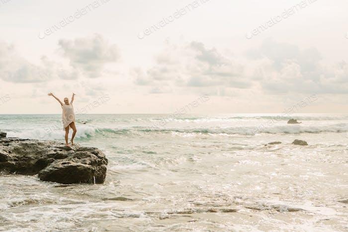 Pretty woman near danger rocks on ocean shore.