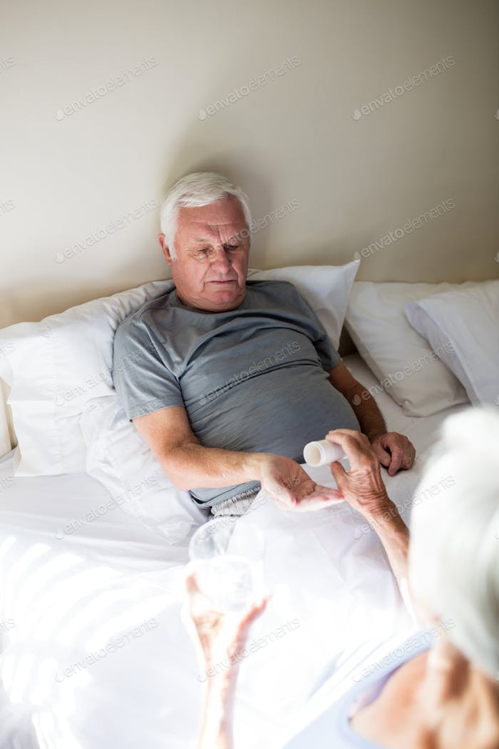 Senior woman giving medicine to senior man in the bedroom