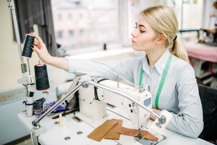 Female dressmaker sews on serger machine