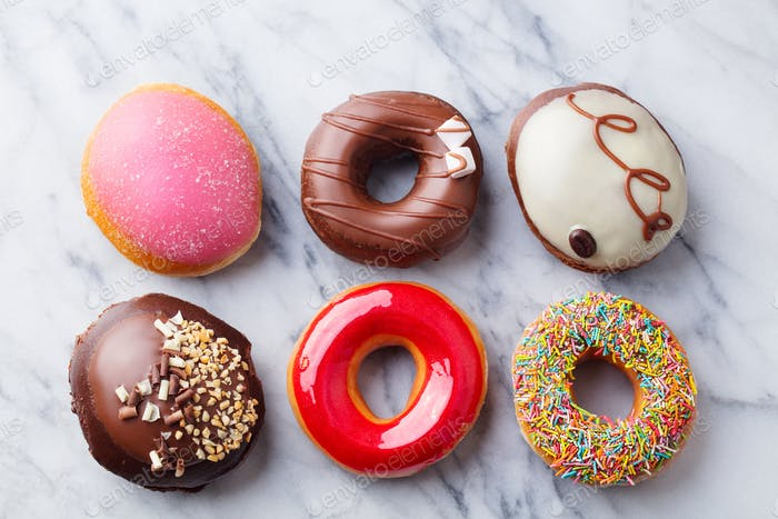 Assortment of Donuts on Marble Table Background. Top view.