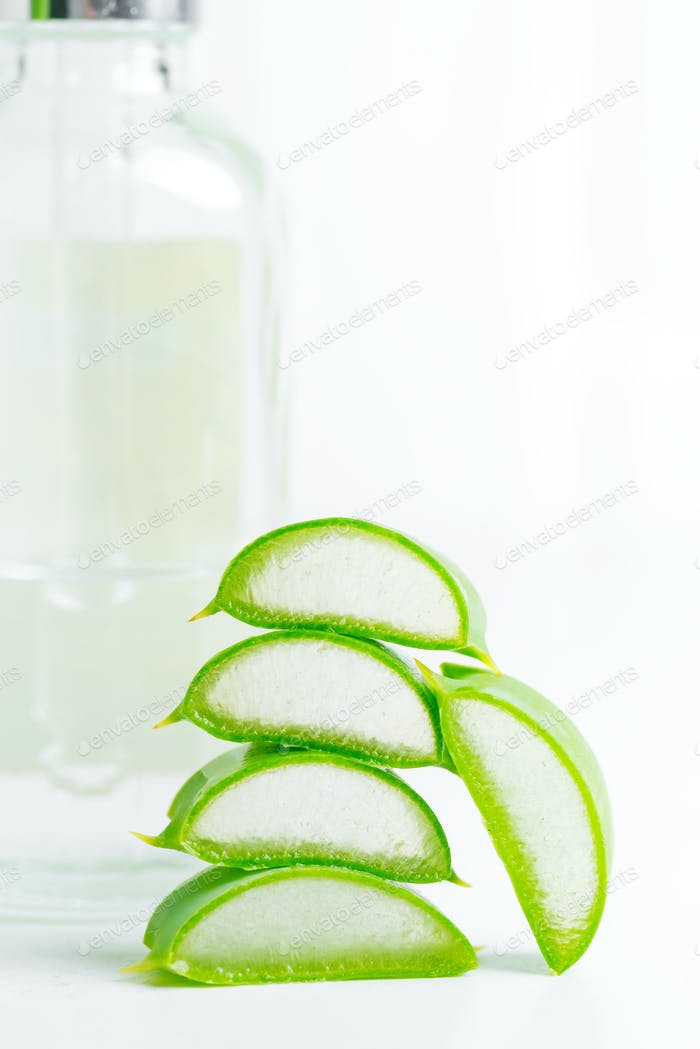 Cosmetic homemade lotion or essential oil from natural sliced aloe vera plant in glass bottles