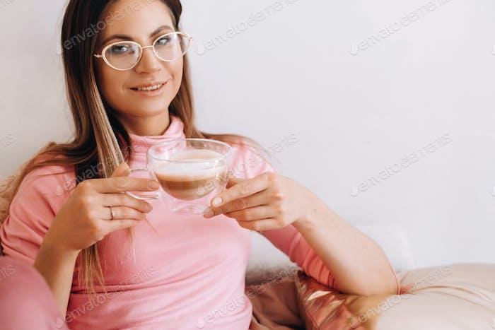 entspanntes Mädchen am Morgen im Schlafanzug zu Hause trinken Kaffee .Innerer Frieden.Das Mädchen sitzt