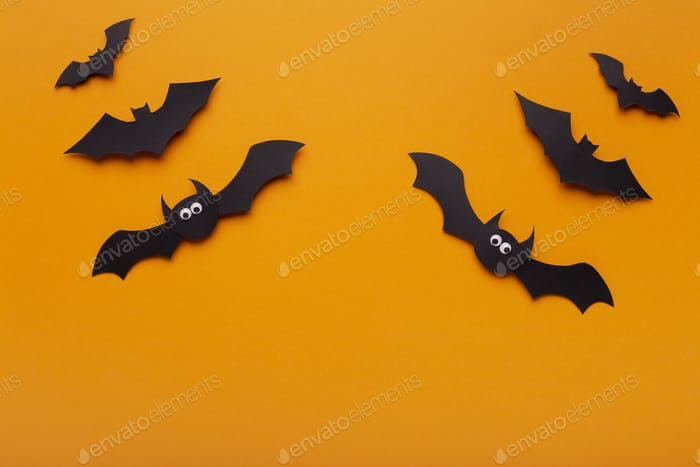 Creative composition of Halloween bats on orange background