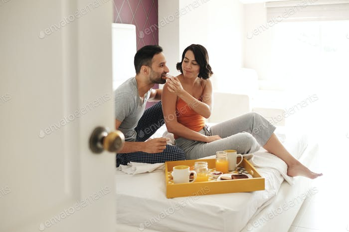 Happy Husband And Wife Eating Breakfast In Bed