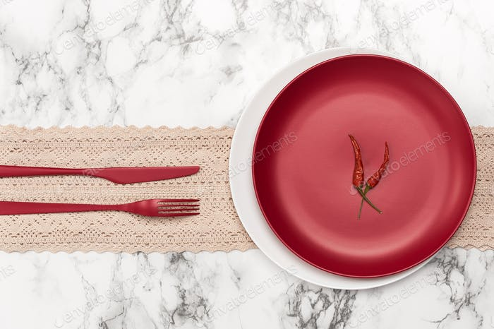 A red plate, cutlery and two chili peppers on a marble table.