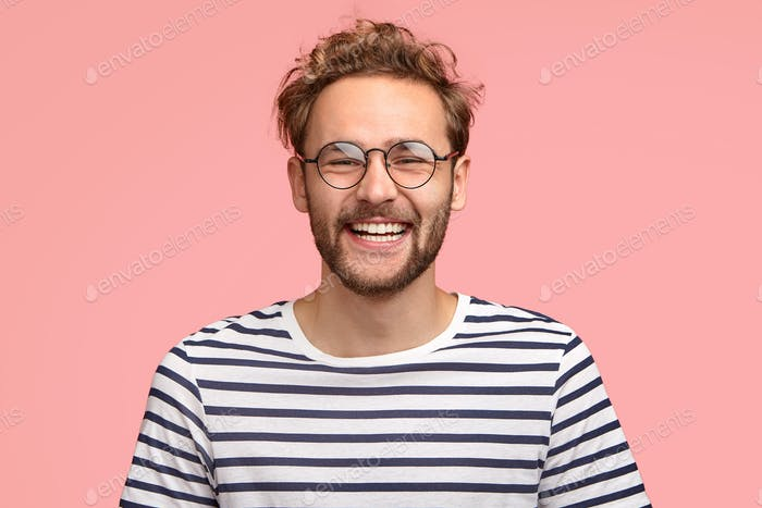 Headshot of pleased hipster has satisfied expression, curly hair and bristle, wears round transparen