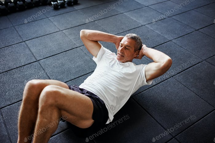 Focused senior man doing an ab workout in a gym