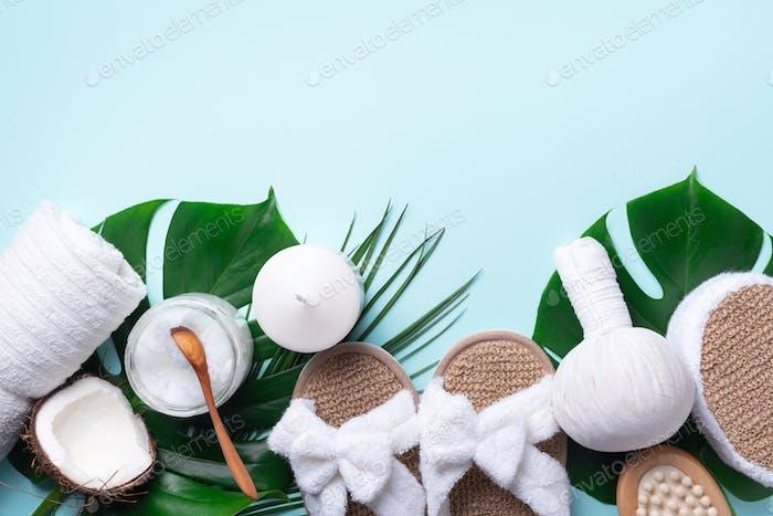 Herramientas de spa: toalla blanca, zapatillas de bambú, bola de hierbas, crema, cepillo de De madera, aceite de coco, monstera en