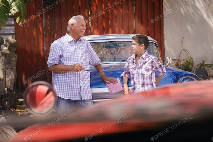 Grandfather Telling History Of Vintage Car To Grandson