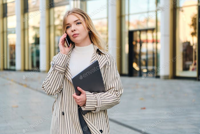 Young attractive businesswoman with laptop confidently talking on cellphone waiting on city street
