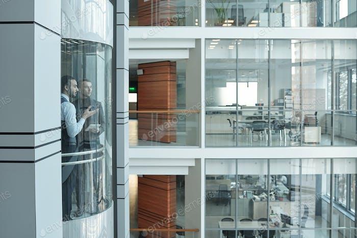 Dos jóvenes oficinistas interculturales contemporáneos que hablan en el ascensor