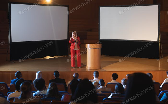 Businesswoman standing near podium and giving presentation to the audience in auditorium