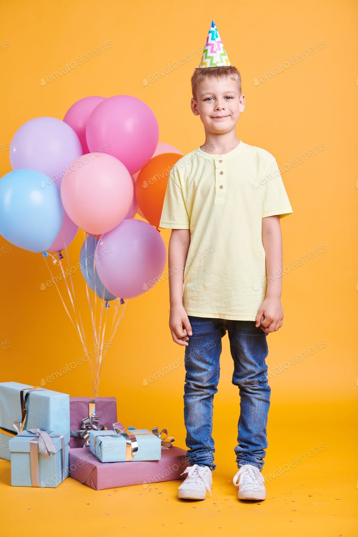 Cute little boy in birthday cap, jeans and yellow t-shirt