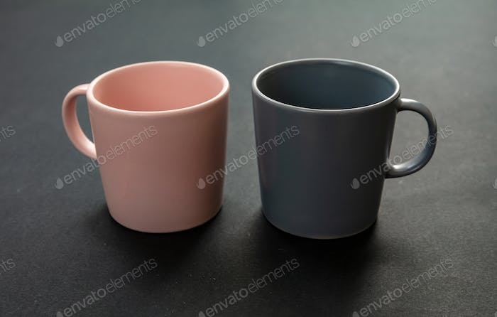 Coffee mugs pink and grey color on black background. Hot beverage cup mockup template