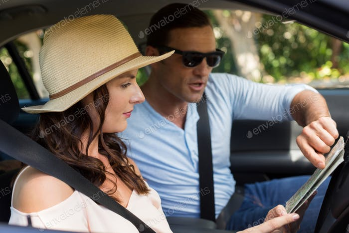 Couple reading map in car