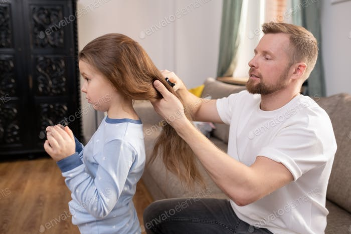 Young careful father with hairbrush brushing long hair of his little daughter