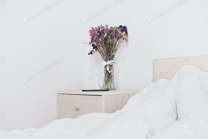 Flor en la mesita de noche en un dormitorio claro