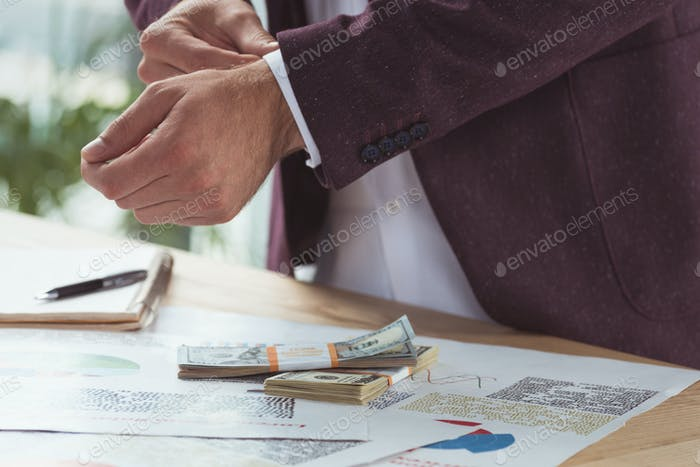 cropped view of businessman with paperwork and dollar banknotes, salary concept