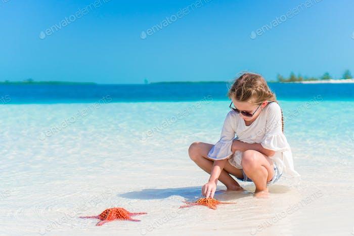 Adorable niña con estrellas de mar en playa blanca