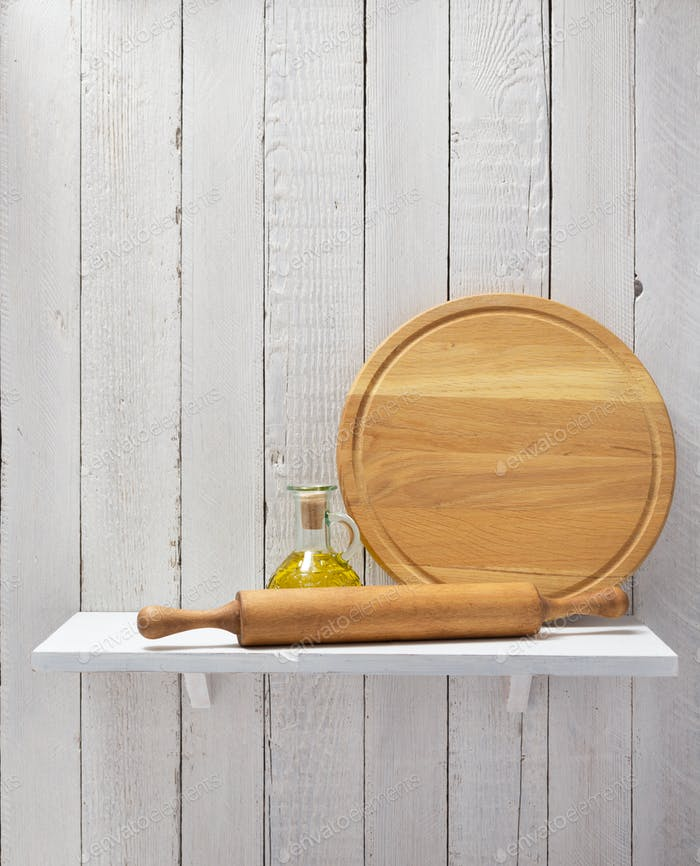 cutting board and oil at wooden shelf