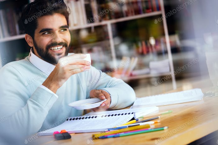 Portrait of young guy drinking coffee while studying in cafe