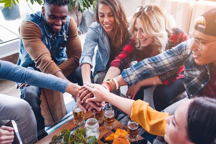 Grupo de amigos mixtos con un montón de manos mostrando unidad y trabajo en equipo.